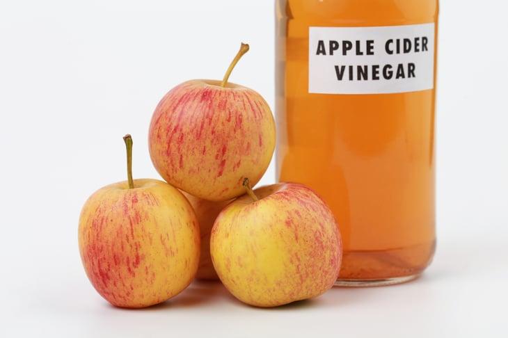 Apple cider vinegar next to a stack of apples