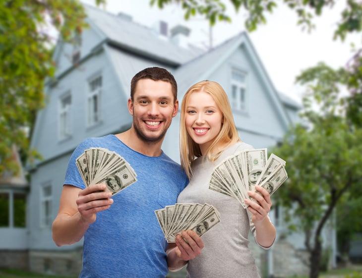 Couple outside home, holding cash.