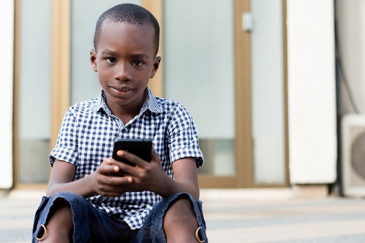 Young African American boy with cellphone, sitting on steps.
