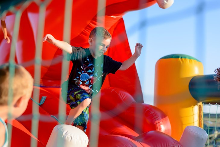 Small boy jumping in inflatable playhouse.