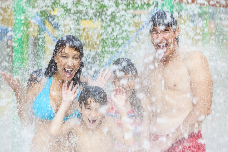 Parents and two kids getting doused at water park.