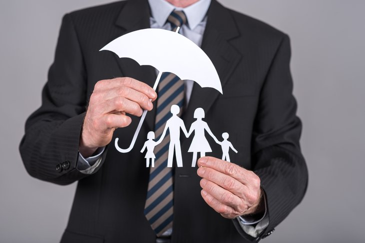 Man holding paper umbrella over paper cutting family