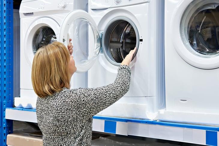 Woman looking at washing machines.