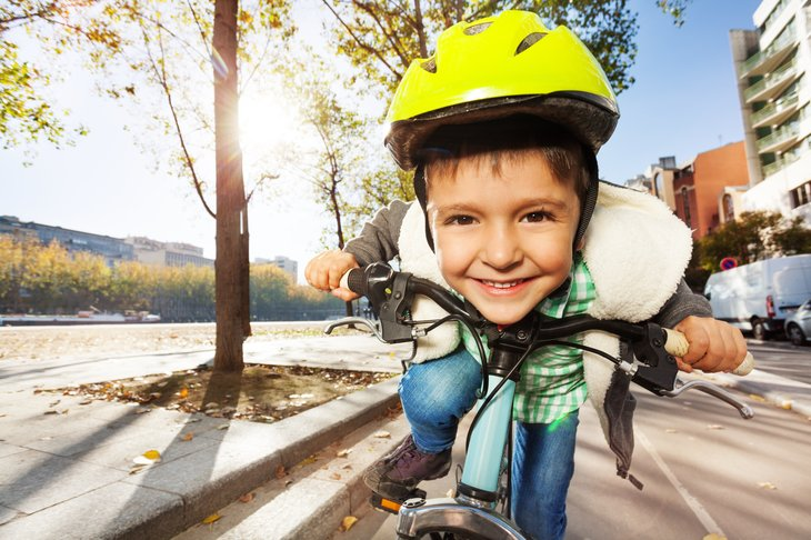 Close up of boy's face as he rides his bike.