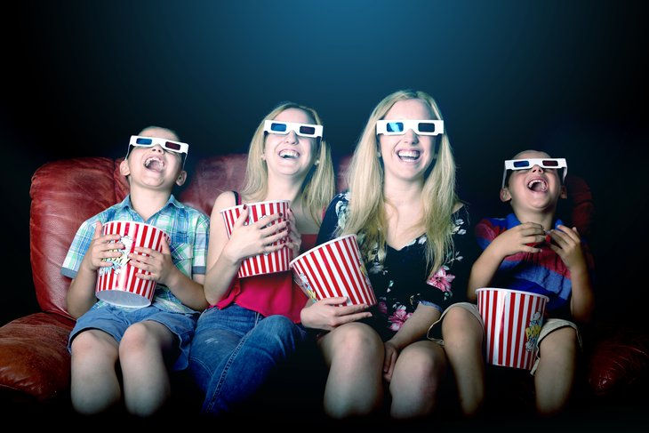 Mom and three kids wearing 3-D glasses, eating popcorn