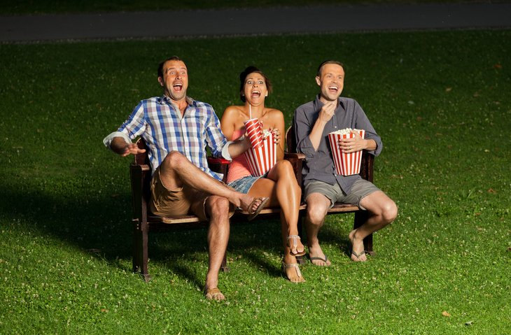 Three adults on a bench eating popcorn