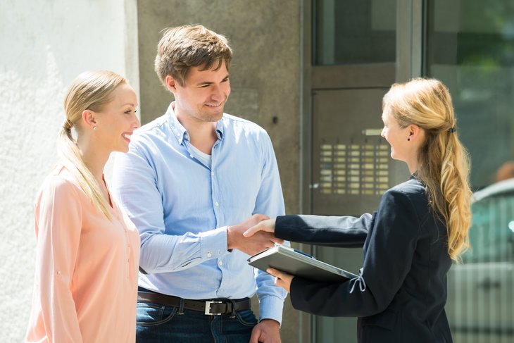 Couple shaking hands with realtor.