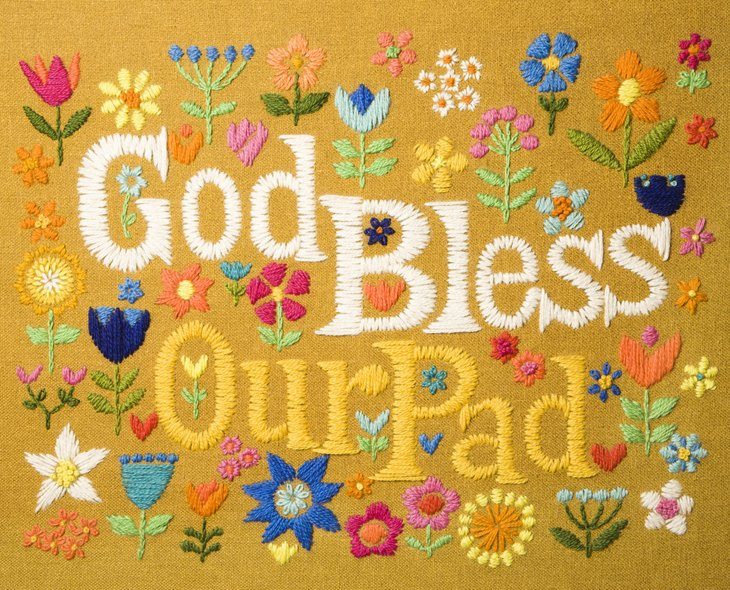 """Needlepoint """"God Bless Our Pad"""" hanging."""