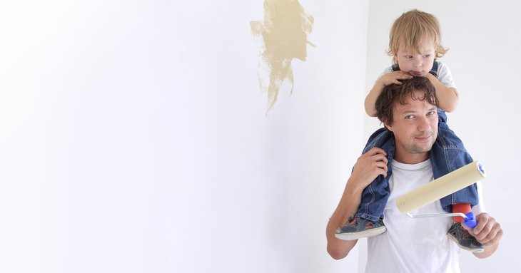 Man painting room with child on shoulders