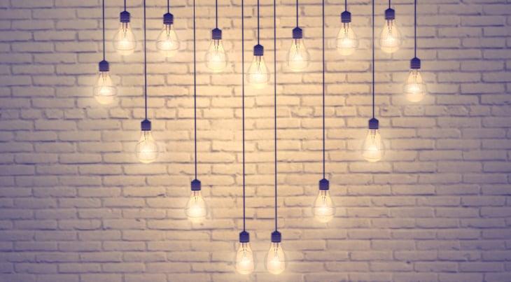 Lightbulb pendants forming a heart against a brick wall.