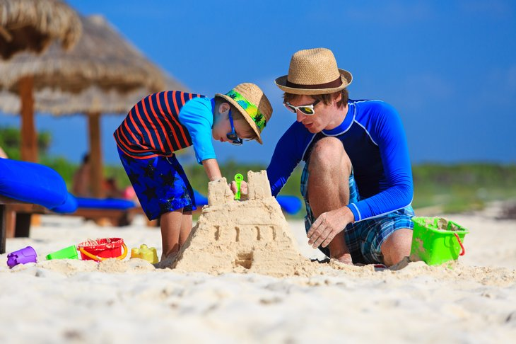 Father and son building sand castle on beach.