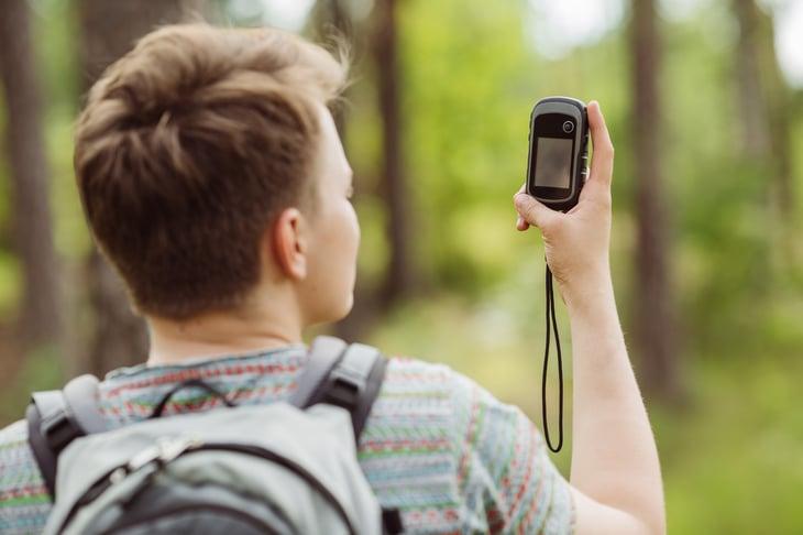 Teen looking at GPS in woods