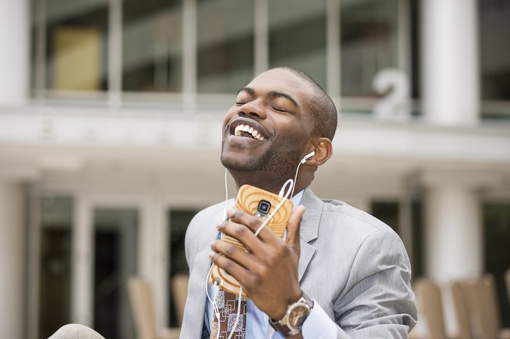 Businessman listening to music on his smartphone