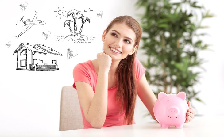 Young woman with piggybank daydreaming.