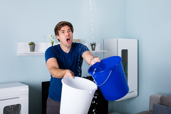 Man holding two buckets catching water leaking from ceiling.