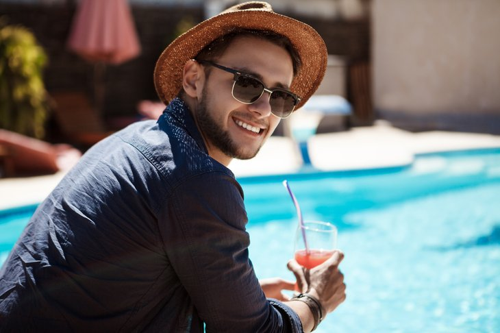 Man in sunglasses by swimming pool