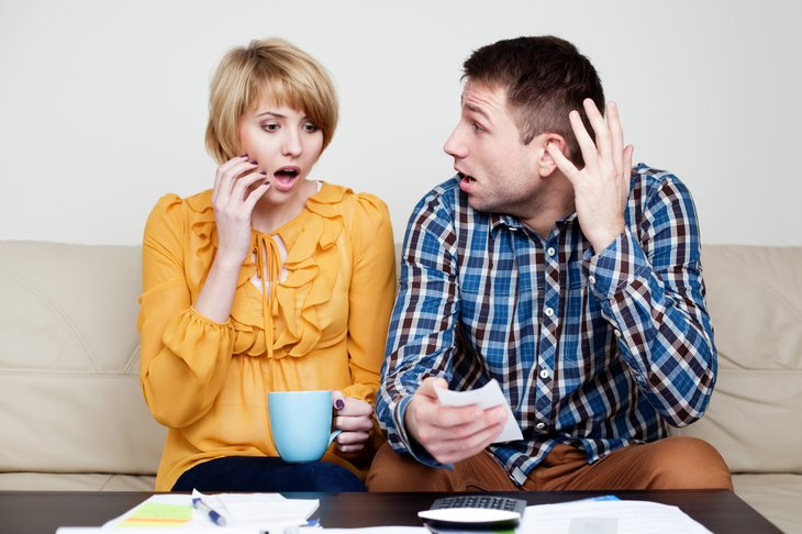 Couple looking at bills, appearing shocked.