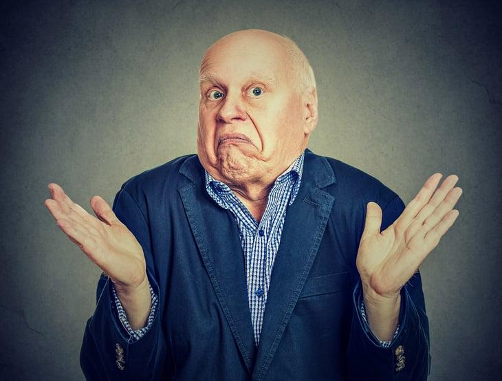 """Older man shrugging shoulders in """"I don't know"""" expression."""