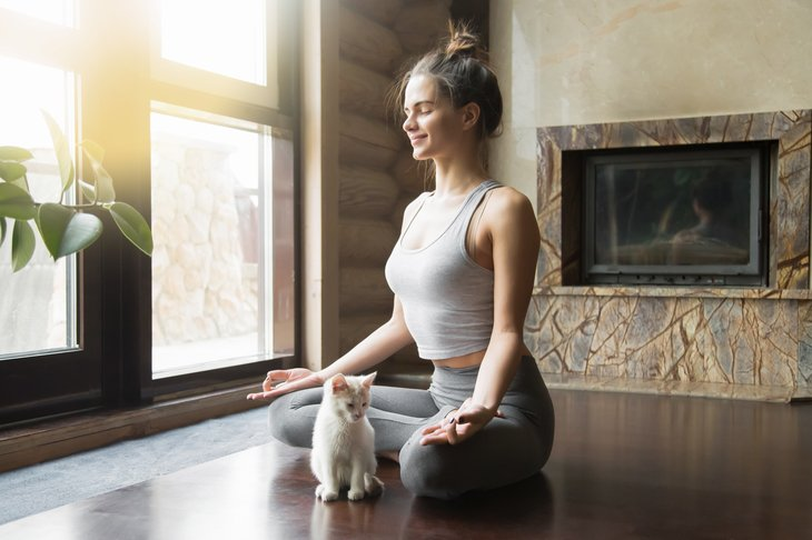 Woman in lotus position with cat.