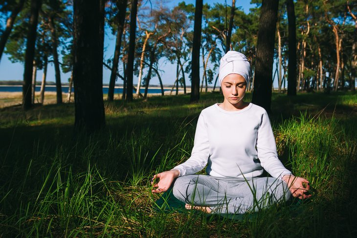 Woman meditating in grass.