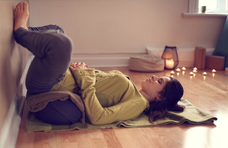 Woman practicing restorative yoga.