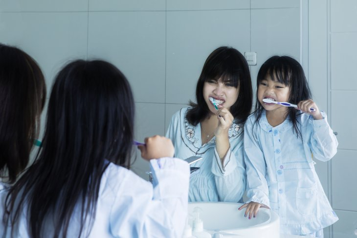 Mom and daughter brushing teeth together,