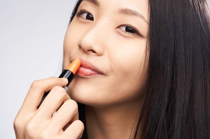 Asian woman applying lipstick