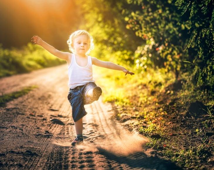Child playing along a dusty path.