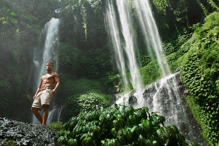 Picture of shirtless man in front of waterfall.