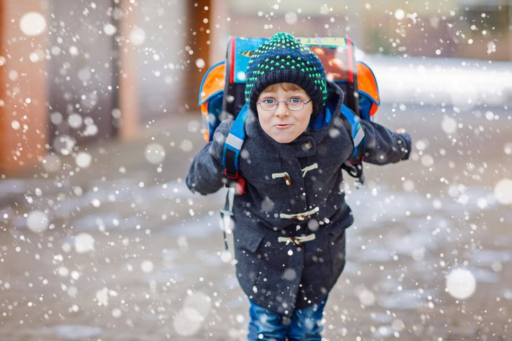 Schoolboy with backpack in snow.