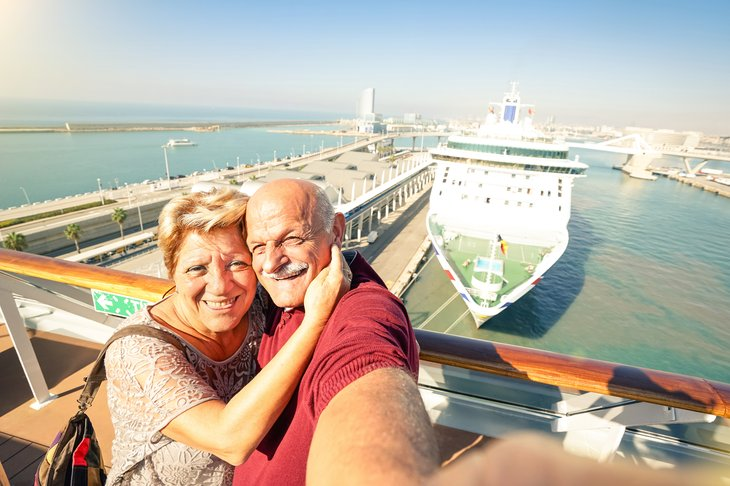 Senior couple taking a selfie on deck of a ship.