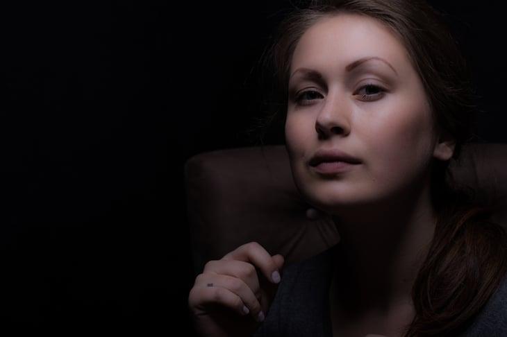 Portrait of a woman against black background