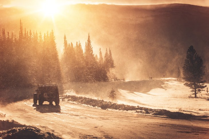 Jeep driving on mountain road in winter