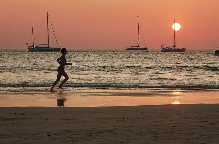 Person running along a beach at sunset.