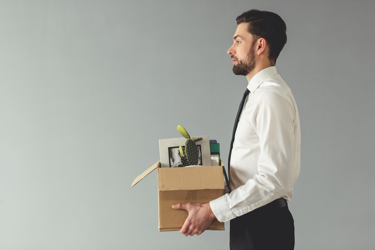 Businessman carrying a box of belongings