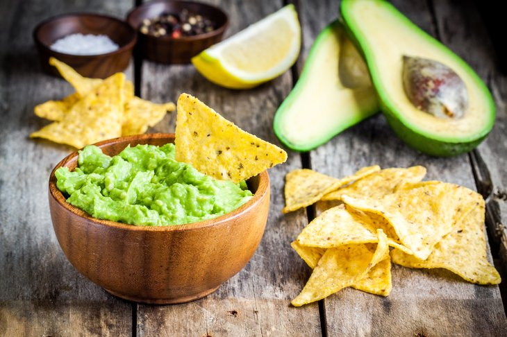 Bowl of guacamole dip with chips and avocados.