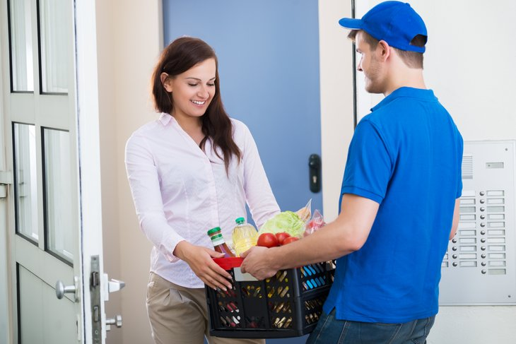 Woman receiving grocery delivery.