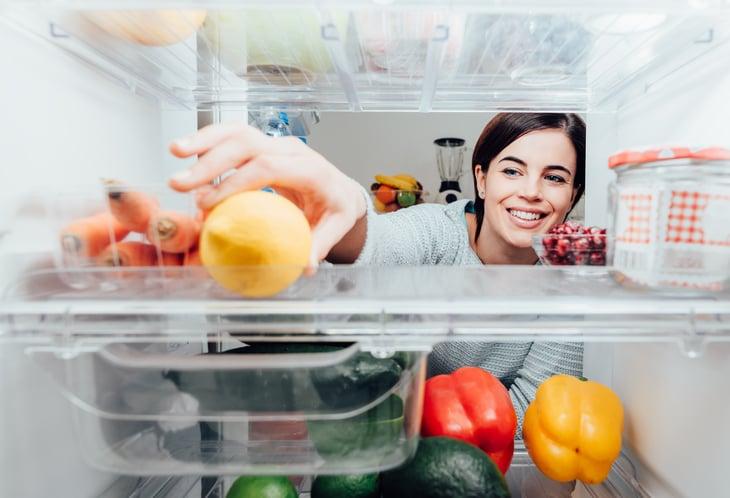 Woman reaching in refrigerator.