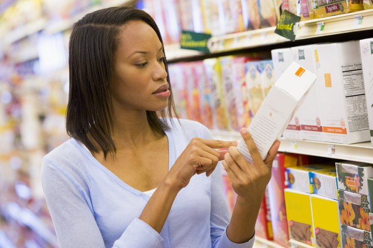 Woman examining food label in grocery store.