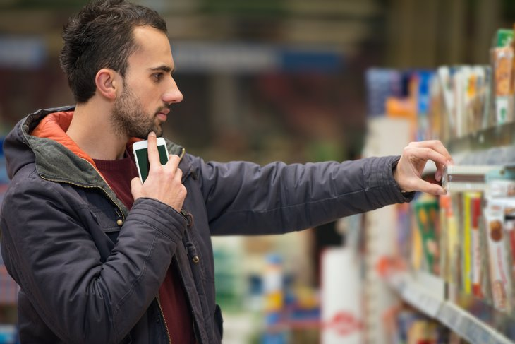 Man looking at groceries in store.
