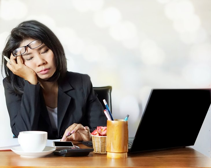 Woman falling asleep at desk.