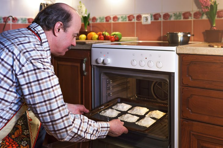 Man removing pies from oven.