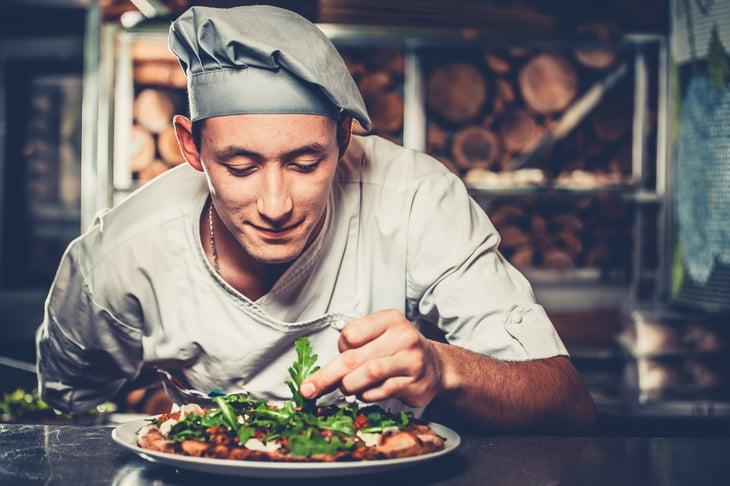 Chef looking at food.