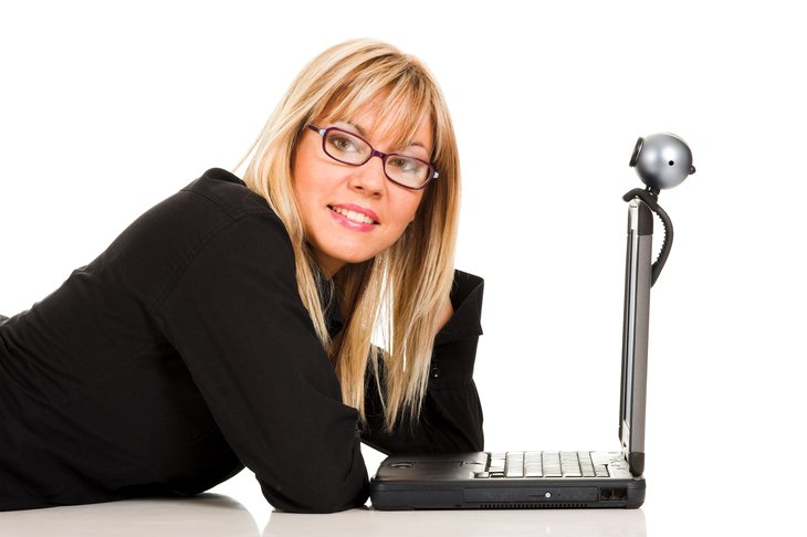 Woman with laptop and webcam.