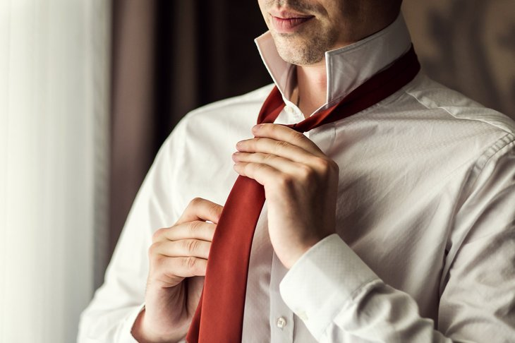 Man in white shirt putting on a tie.