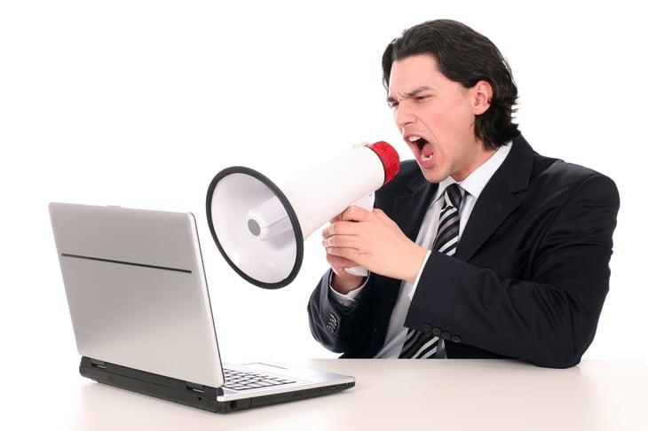 Man shouting through megaphone at computer.