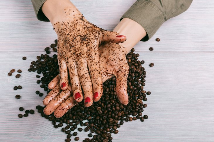 A woman scrubs her hands clean with coffee grounds