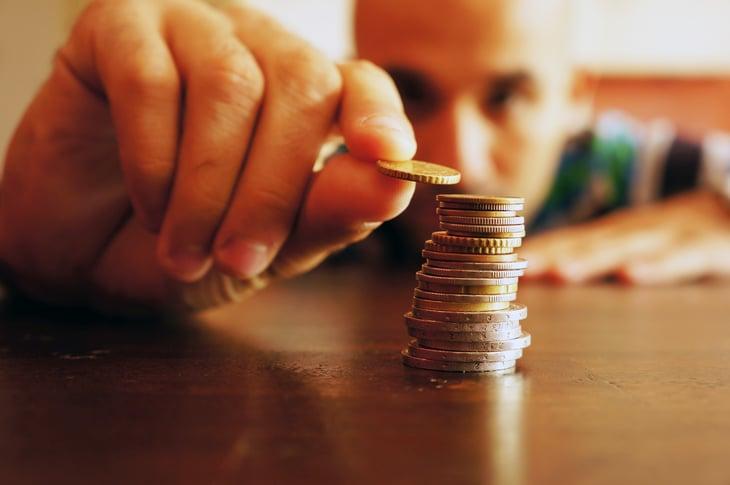 Man stacking coins at eye-level.