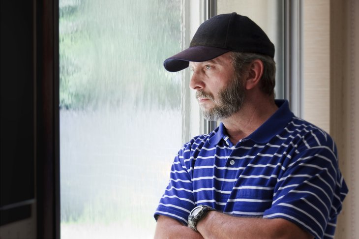 Middle aged man looking out window, with pensive expression.
