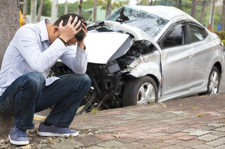 Upset man by smashed car.